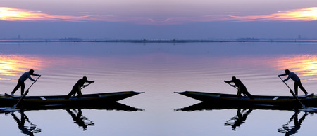 Venice sunset symmetrical silhouette of sinchronized rowing men