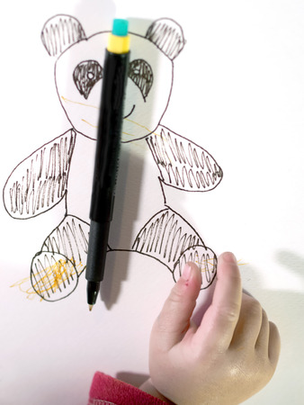 child hand scribbling a drawing of a teddy bear