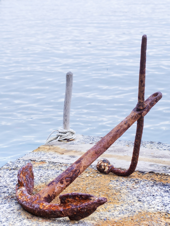 Old rusty anchor on the dock near the sea
