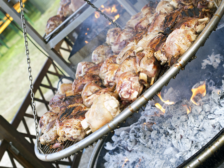 brazier: roasted pork knuckle  on  large brazier in country fair