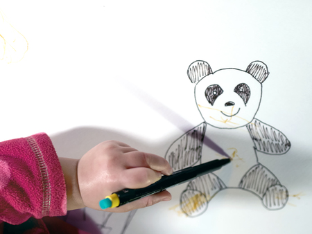 scribbling: child hand scribbling a drawing of a teddy bear