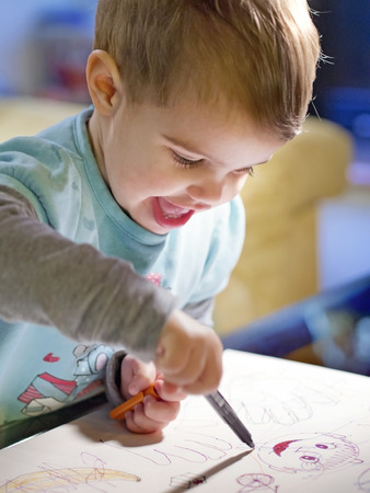 baby girl smiles as she scribbles a sketchbook at home