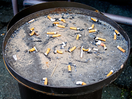 Cigarette butts in a container outdoor ashtray