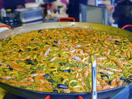 great pan of Spanish paella squid and vegetables Stock Photo