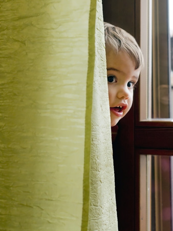 little girl hides behind a curtain in her home Stock Photo