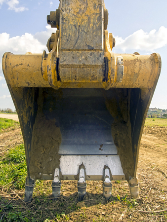 yellow excavator bucket on the land in the country