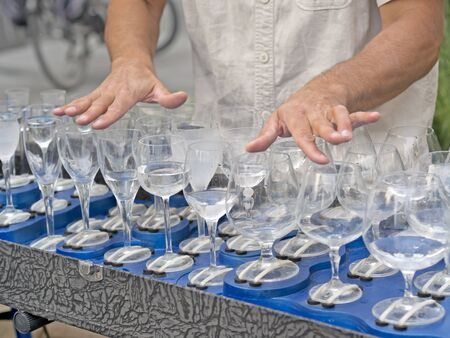 chalices: busker playing filled crystal glasses of water  with fingers Stock Photo