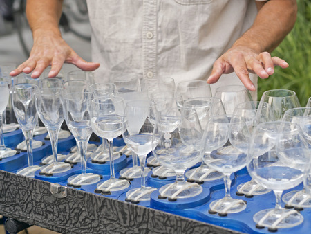 busker playing filled crystal glasses of water  with fingers Stock Photo