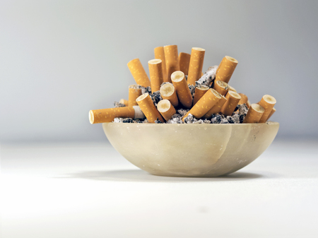the habit of smoking cigarettes and fill  ashtray