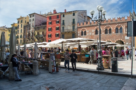 april 26 2012 Verona, Italy Piazza Herb Market day view of the tower and view of the palace maffei People at the market square of grass
