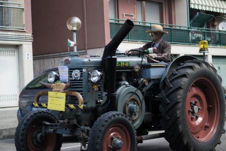 Staruszek jazdy starego ciągnika na drodze Publikacyjne