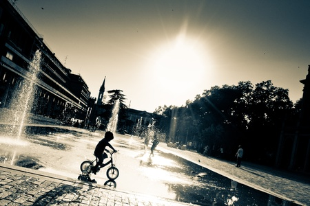 a child on the tricycle ride against the fountains photo