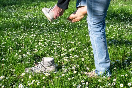 person who takes off his shoes in a field of daisies