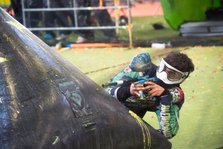 bologna,Italy-June 15,2013 young boy playing paintball shooting and sheltering behind a protection during a competition in Italy