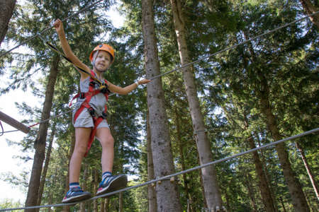 child with helmet and safety ropes walks among the trees on ropes Stock Photo
