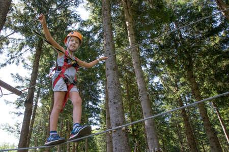 Dziecko z kaskiem i bezpieczeństwa lin spacery wśród drzew na linach Zdjęcie Seryjne