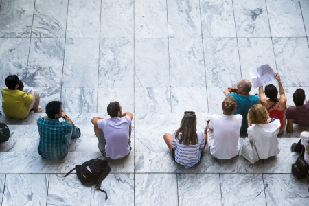 New York City, USA - August 2, 2013 people sitting on white steps to rest and talk to each other in top view
