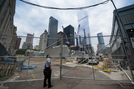 New York City, USA - August 3, 2013 a person admires the construction site of World Trade Center tower over Ground Zero Lower Manhattan  through the intersection of Albany and Greenwich Streets
