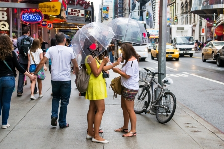 New York City, USA - August 3, 2013 girls with umbrellas walk between the traffic and billboards time square in a rainy day