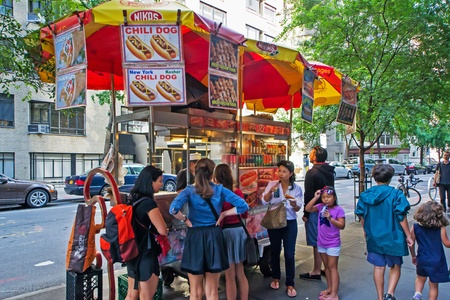 characteristic: New York City, USA - August 3, 2013 People queuing at a characteristic fast food hot dog stand near the museum of modern art in new york  This fast food mobile stands are very popular all over Manhattan  Editorial