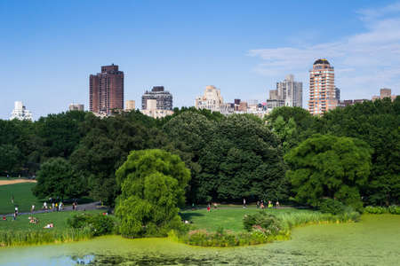 New York City, USA - August 3, 2013 view of some skyscrapers from one of the many lakes found in central park in new york people come here to relax and practice outdoor sports