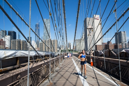 get across: New York City, USA - August 4,2013 tourists and New Yorkers across the Brooklyn Bridge every day for sports, sightseeing or simply to get to work
