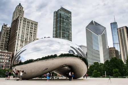 Chicago,USA-august 12,2013 Tourists take pictures and admire the skyline of chicago through the famous monument  Cloud Gate  in the Millennium Park