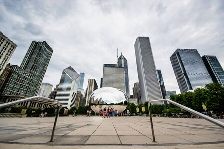 distorted image: Chicago,USA-august 12,2013 Tourists take pictures and admire the skyline of chicago through the famous monument  Cloud Gate  in the Millennium Park