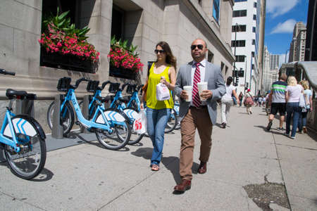Chicago,USA-august 13,2013 People stroll on michigan avenue next to the classic blue bike rental  this couple have the classic tall glasses walking