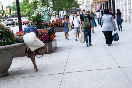 settles: Chicago,USA-august 13,2013 woman settles a shoe on michigan avenue in chicago in a sunny day