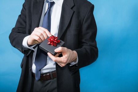 elegant man handing a gift with a red ribbon
