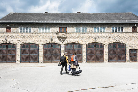 concentration camp: mauthausen, Austria - May 10,2014 two people crossing the Mauthausen camp with camera equipment to film a documentary on the Austrian concentration camp during a cloudy day  Editorial