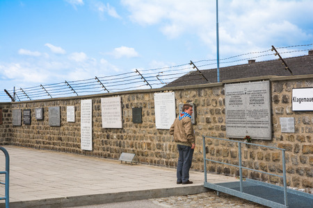perpetrator: mauthausen,Austria-May 10,2014 Man looks at the commemorative plaques inside the concentration camp Mauthausen in Austria during a cloudy day  Editorial