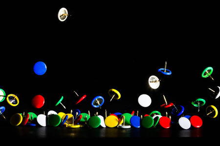 jumping colored pins on a dark background