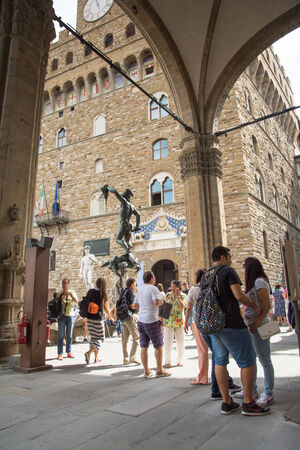Florence,Italy-august 26,2014:many tourists in Piazza della signoria take pictures, buy souvenirs or enter in the Palazo vecchio during a sunny day.Palazzo vecchio in one of the symbols of Florence.