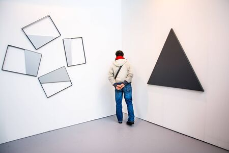 annual event: Bologna,Italy-January 24,2015:a visitor observes the description of some works of art at the annual event called Artefiera held in Bologna-Italy.