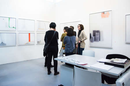 Bologna,Italy-January 24,2015:people walk and look at works of art in an exhibition while art experts answer all questions related to the artists on display.