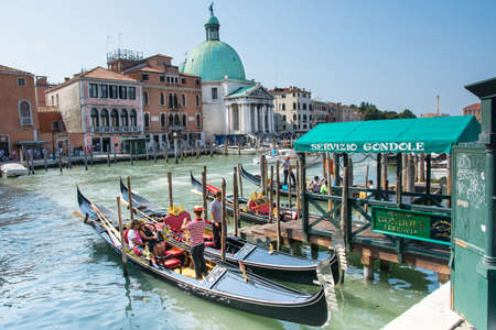 gondoliers: Venice,Italy-August 12,2014:gondolas ready to carry around tourists through the Venice canals during a sunny day.