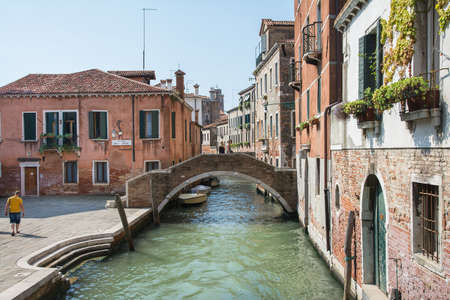 gondoliers: Venice,Italy-August 12,2014:commercial and touring boats navigate the canals of Venice during a summer day.This is one of  hidden corner of Venice. Editorial