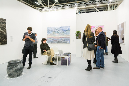 art exhibition: Bologna, Italy-January 24.2015: people walk and look at works of art in an art exhibition while experts answer all questions related to the artists on display.
