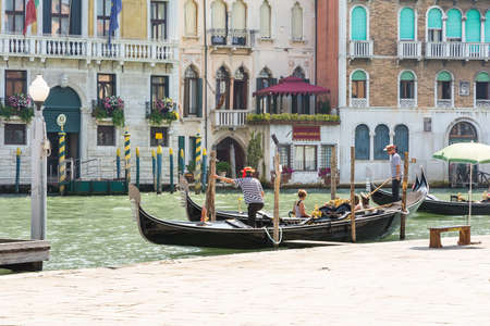 await: Venice,Italy-August 12,2014:Venetian gondoliers await some tourists to carry around on a gondola in Venice During a sunny day.