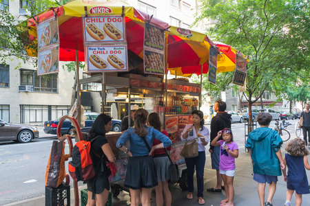 New York City, USA - August 3, 2013:People queuing at a characteristic fast food hot dog stand near the museum of modern art in new york..This fast food mobile stands are very popular all over Manhattan. Redactioneel