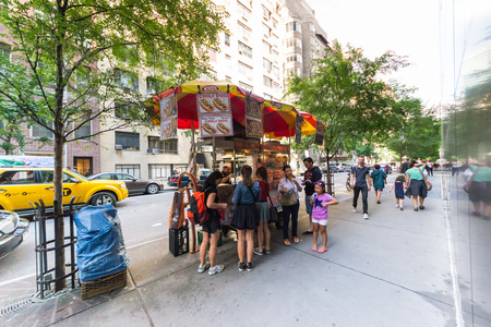 characteristic: New York City, USA - August 3, 2013:People queuing at a characteristic fast food hot dog stand near the museum of modern art in new york..This fast food mobile stands are very popular all over Manhattan. Editorial