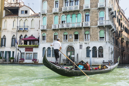 gondoliers: Venice, Italy-August 12.2014: Venetian gondoliers to carry around some tourist on a gondola in Venice During a sunny day. Editorial