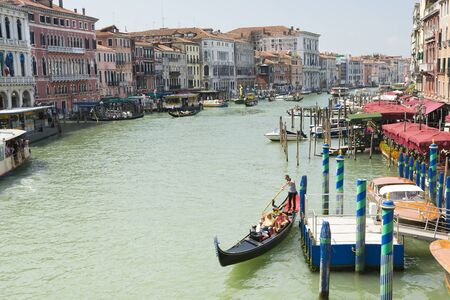 await: Venice, Italy-August 12.2014: Venetian gondoliers await some tourists to carry around on a gondola in Venice During a sunny day.