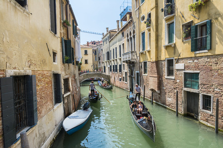 gondoliers: Venice,Italy-August 12,2014:Venetian gondoliers carry around some tourists  on a gondola in Venice During a sunny day inside her famous canals.