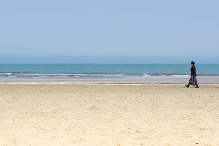 stroll: Rimini,Italy-April 12,2015:A lonely woman stroll on the Rimini beach near the sea during a sunny day.