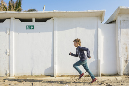 niños abandonados: Rimini, Italia-abril 12,2015: A los niños correr frente a las antiguas cabañas abandonadas en la playa en Italia.