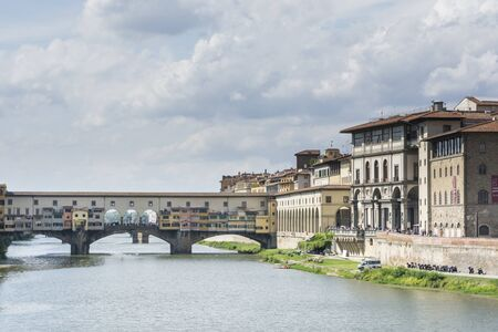 florence italy: Florence, Italy August 26.2014: a picturesque view of the Uffizi Gallery and the Ponte Vecchio bridge over the Arno River in Florence-Italy During a sunny day.