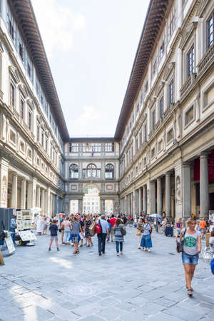 florence italy: Florence, Italy – August 26,2014:Many tourists strolling in the Uffizi gallery in the middle of the street artist or to go to the museums during a cloudy day. Editorial